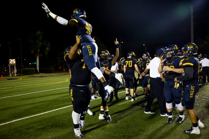 Naples High School's Josiah Goberman lifts Handel Victor into the air after beating South Fort Myers High School 63 to 0 on Friday, October 19, 2018, at Naples High School in Naples.
