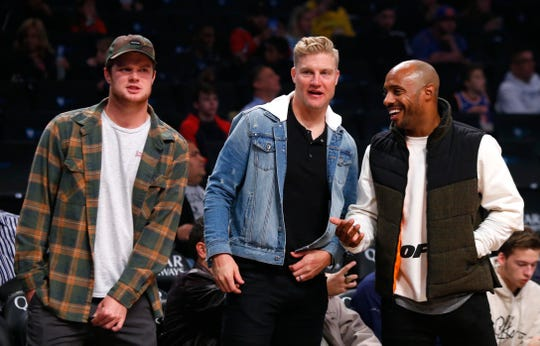 Oct 19, 2018; Brooklyn, NY, USA; New York Jets quarterbacks Sam Darnold (left) and Josh McGowan (middle) and former NBA basketball player Jay Williams (right) react at Barclays Center.