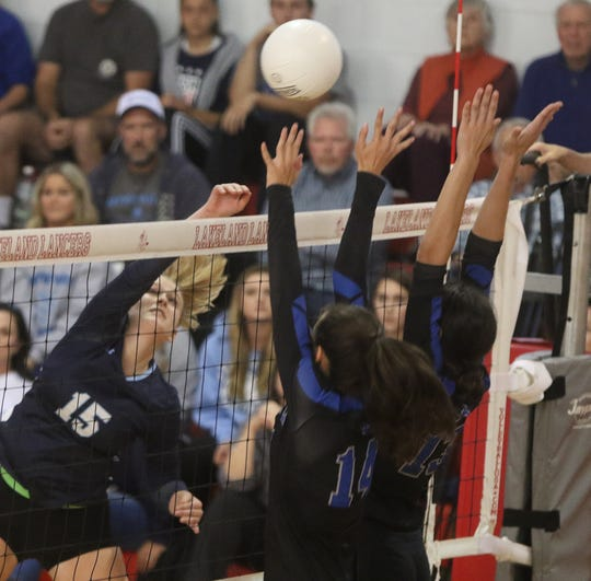 Molly McAtee of Wayne Valley hits the ball over Jenna Abreau and Ashley Martinez of Passaic tech.