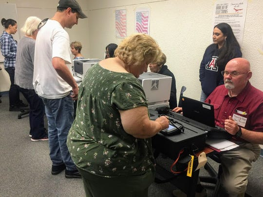 A county resident signs up to early vote at Thomas Branigan Memorial Library, 200 E. Picacho Ave., Saturday, Oct. 20, 2018.