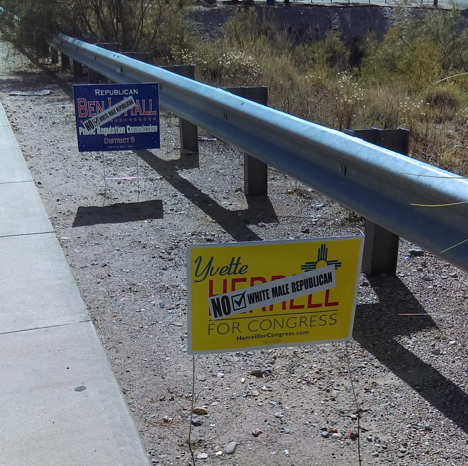 Stickers decrying white males placed on Yvette Herrell political sign