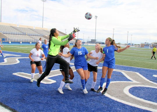 Carlsbad's Taighen Whitzel (15) and Gabby Aragon (1) try to head the ball before Roswell's goalie can stop the ball in the first half of Saturday's game. The Cavegirls won, 9-0.