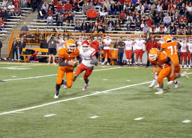 Artesia quarterback Trent Taylor (14) scrambles to buy himself time before throwing  touchdown pass to Braxton McDonald in the first quarter during Friday's game against Roswell.