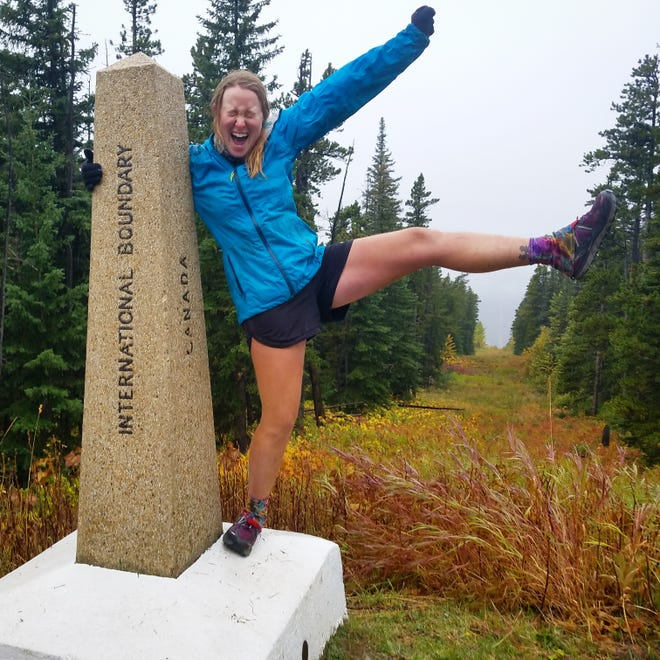 Farmington's Amanda Goldstein celebrates completing the Continental Divide Trail on Sept. 16 at the border between northwest Montana and Canada.