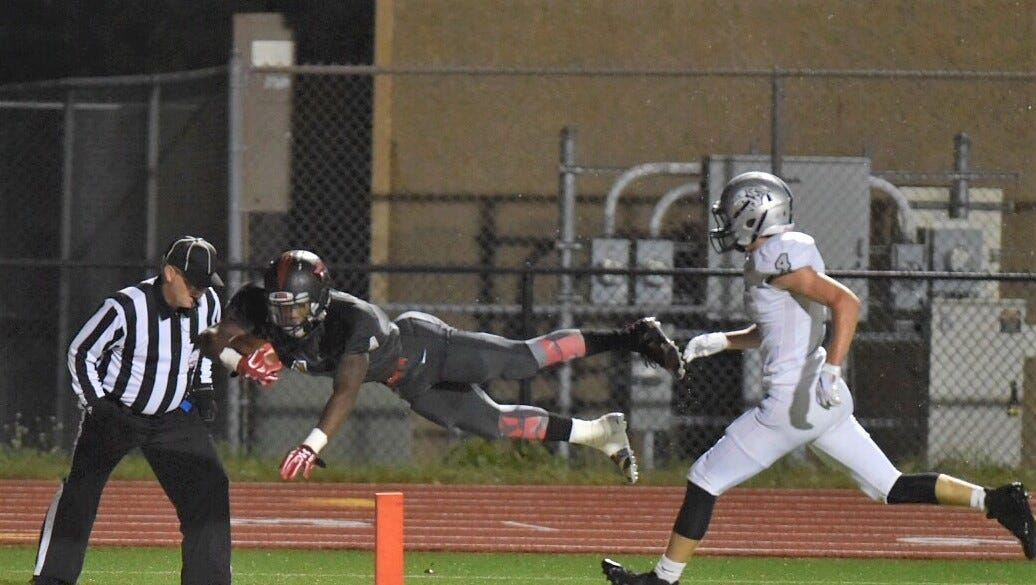 Churchill's Darrell Mason Jr. (left) soars into the end zone for a 24-yard TD run as Plymouth's Nathan Janke trails the play.