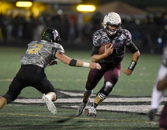 Seaholm QB Gray Kinnie runs the ball as Groves henry Van Faussien goes for the tackle.
