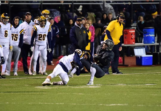 South Lyon's Jake Newman (25) tackles a South Lyon East player. Newman scored a crucial touchdown at the end of the first half, returning a blocked field goal.