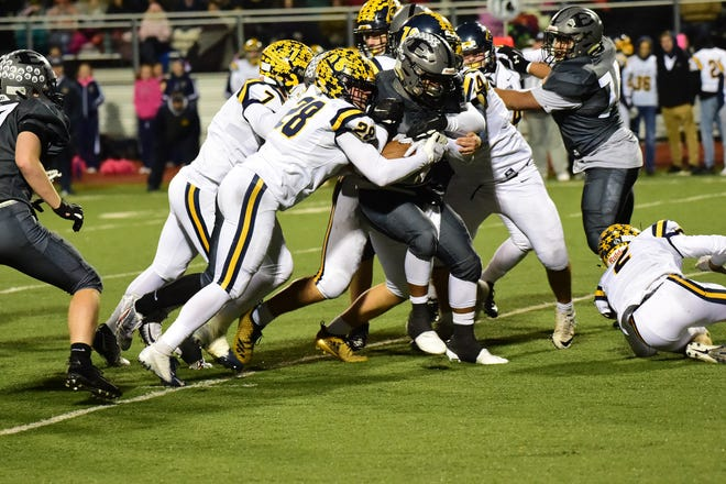South Lyon East running back Donovan Wright (26) is tackled by a group of LIons.