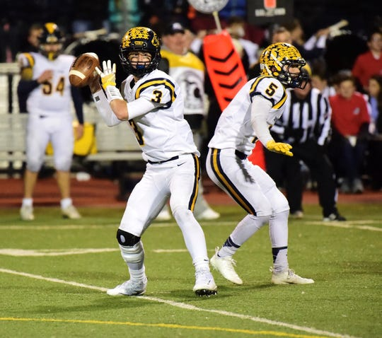 Dropping back to pass is South Lyon junior quarterback Connor Fracassi (3). Blocking for him is senior running back Ian Goins (5).