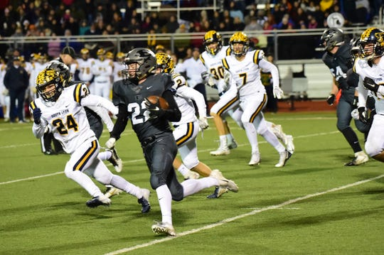 Matt Gilbert (22) is on his way to a 73-yard touchdown run in the first minute of the second half. That briefly regained the lead for South Lyon East.