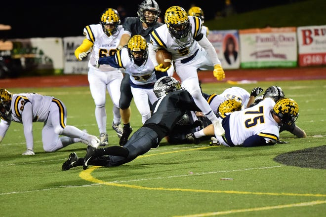 South Lyon senior running back Ian Goins (5) jumps over a Cougars defender for tough yardage.