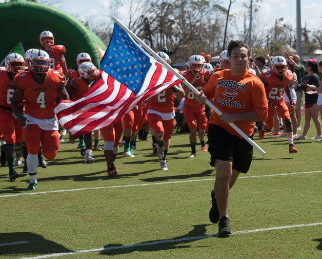 The Panama City Mosley High School football team charges out onto the gridiron to take on Pensacola High School for a rare Saturday, Oct. 20, 2018, game. Billed as a community gathering, the free football game featuring Pensacola High School and Mosley offered those in the hurricane disaster area a chance to relax and decompress from the storm's aftermath.