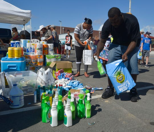 Panama City resident, Thaddeus Evans, picks up donated supplies from the Pensacola High School football team at the Tommy Oliver Stadium on Saturday, Oct. 20, 2018. Billed as a community gathering, the free football game between PHS and Mosley offered those in the hurricane disaster area a chance to relax and decompress from the storm's aftermath.