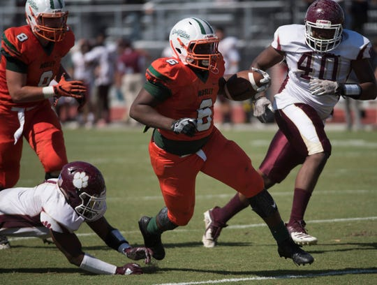Mosley High School's Jacarri Greene, (No. 6) blows through the Pensacola High School defense during Saturday's game in Panama City.