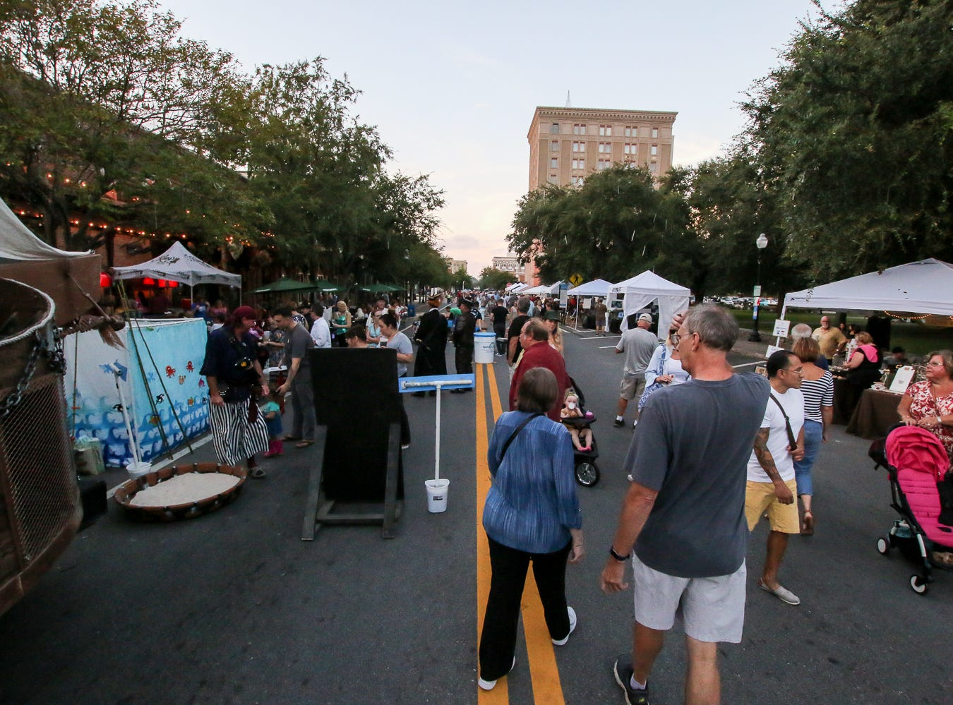 People check out Gallery Night vendors set up near O'Riley's Irish Pub on Friday, October 19, 2018.