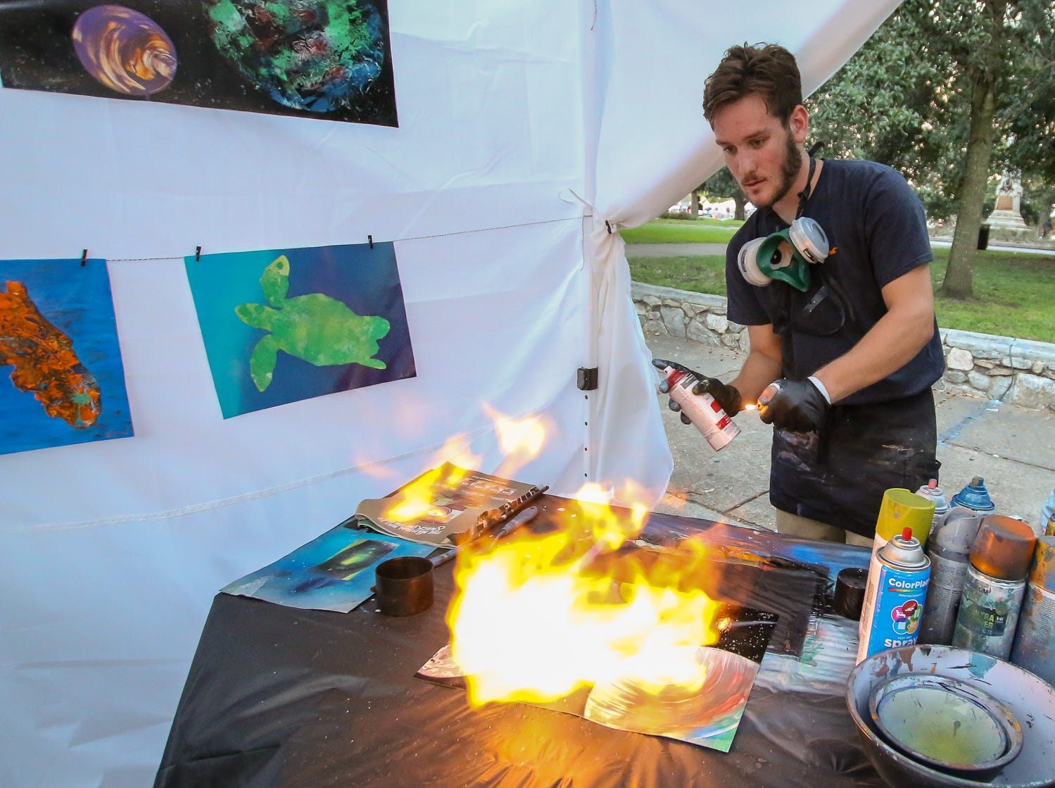 Jordan Wallce sprays fire across one of his paintings during Gallery Night on Friday, October 19, 2018.