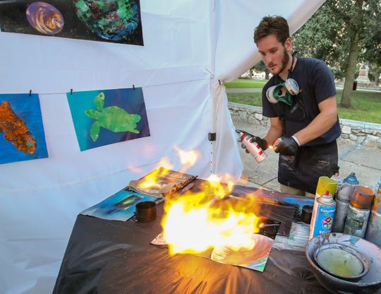 Jordan Wallce sprays fire across one of his paintings during October's Gallery Night. This month's Gallery Night will be Friday.