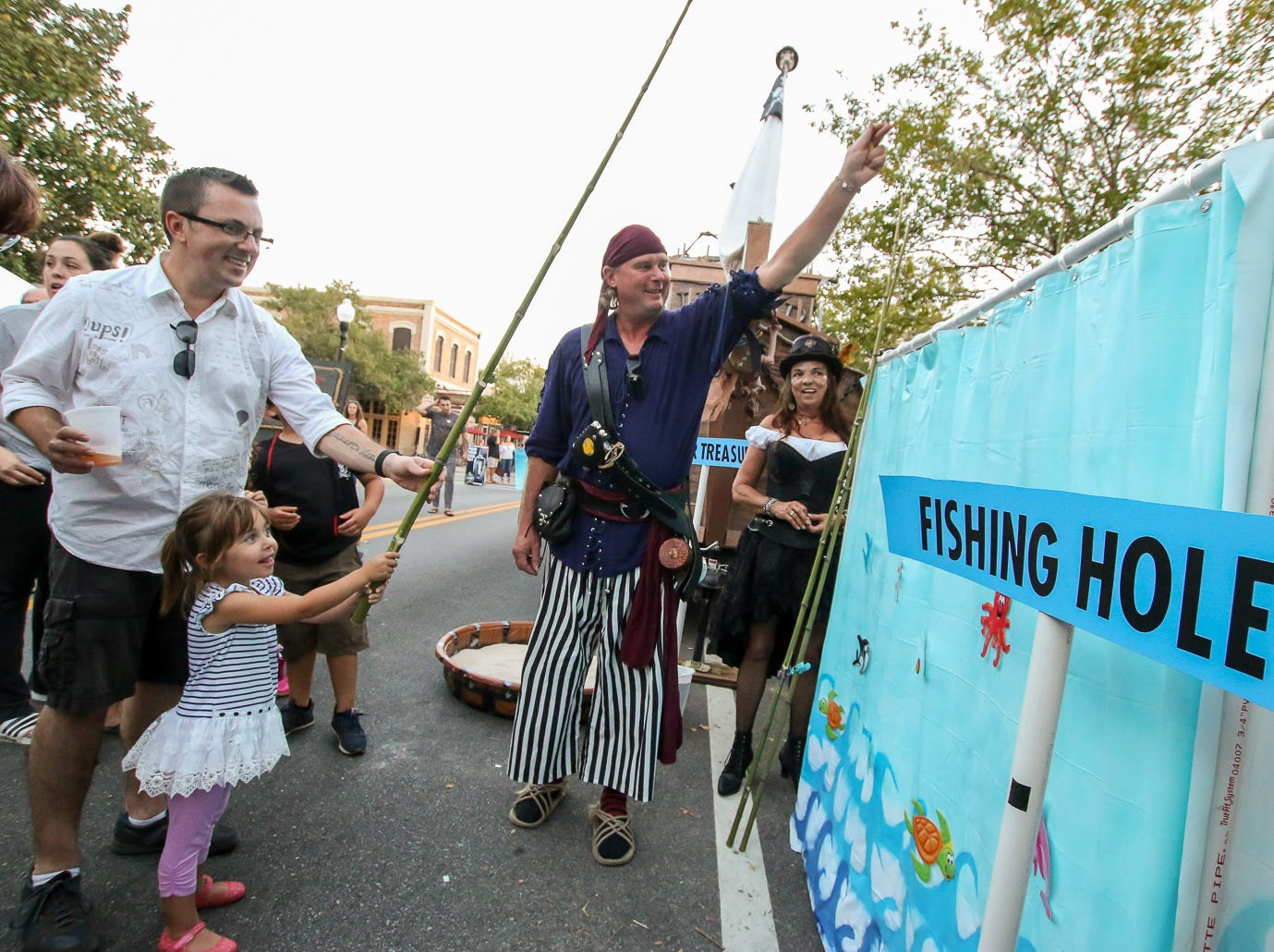 Krewe of Airship Pirates member Steven Helm, center, helps Mila Hietpas, 3, and her dad, Kevin, snag a prize from a pop-up faux fishing hole during Gallery Night on Friday, October 19, 2018.