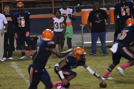 Escambia quarterback AV Smith picks up a fumbled snap during Friday night's game against Lincoln.