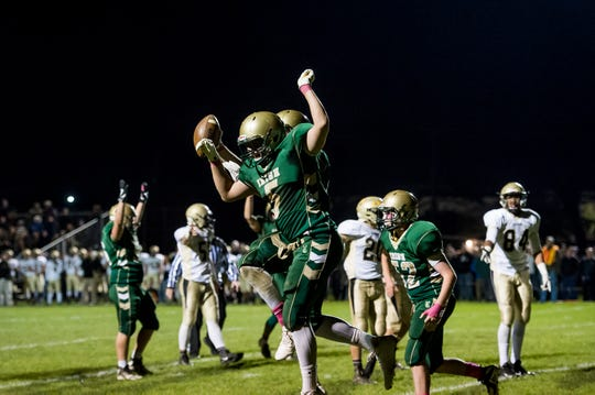 York Catholic's Isaiah Pineda (5) celebrates with Noah Kiel after Kiel scored a touchdown against Delone Catholic on Friday, October 19, 2018. The Fighting Irish won 35-7.