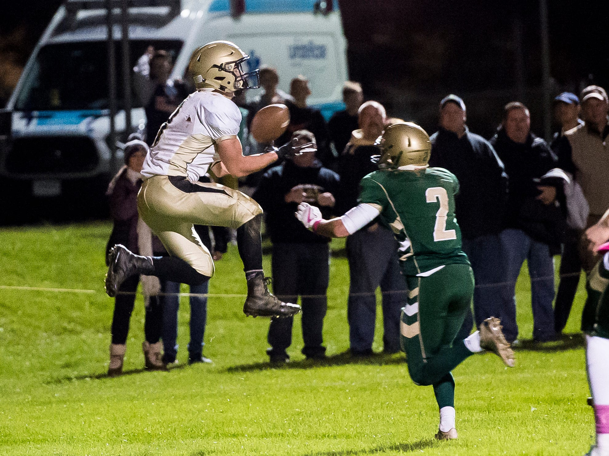 Delone Catholic's Logan Brown leaps in the air to catch to catch a pass and score a touchdown against York Catholic on Friday, October 19, 2018. The Squires fell 35-7.