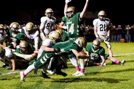 York Catholic's Mitchell Galentine leaps into the end zone to score a touchdown against Delone Catholic on Friday, October 19, 2018.