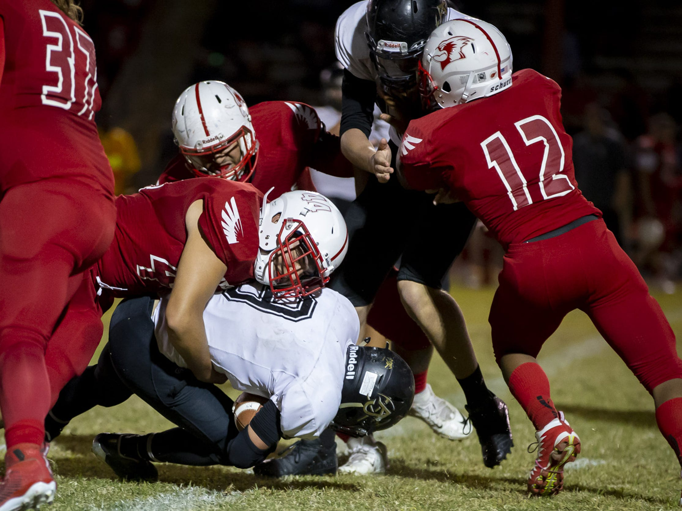 Senior running back William Lohman (9) of the Apache Junction Prospectors is tackled by senior middle linebacker Brannon Lopez (44) of the Glendale Cardinals at Glendale High School on Friday, October 19, 2018 in Glendale, Arizona. #azhsfb