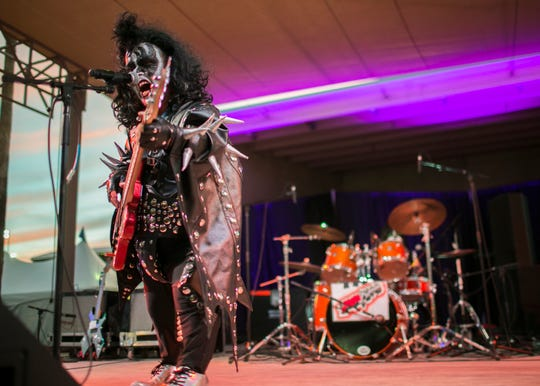 """Brian Thoe, dressed as """"Mini-Gene"""", performs on stage with Mini Kiss at the Arizona State Fair in Phoenix on Saturday, Oct. 6, 2018."""