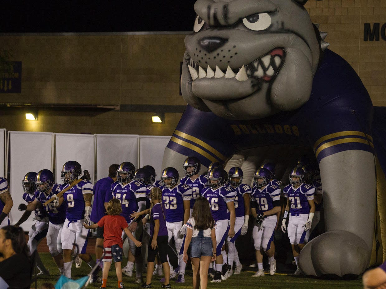 Queen Creek players slap hands with little kids before their game with Highland Friday, Oct. 19, 2018. #azhsfb