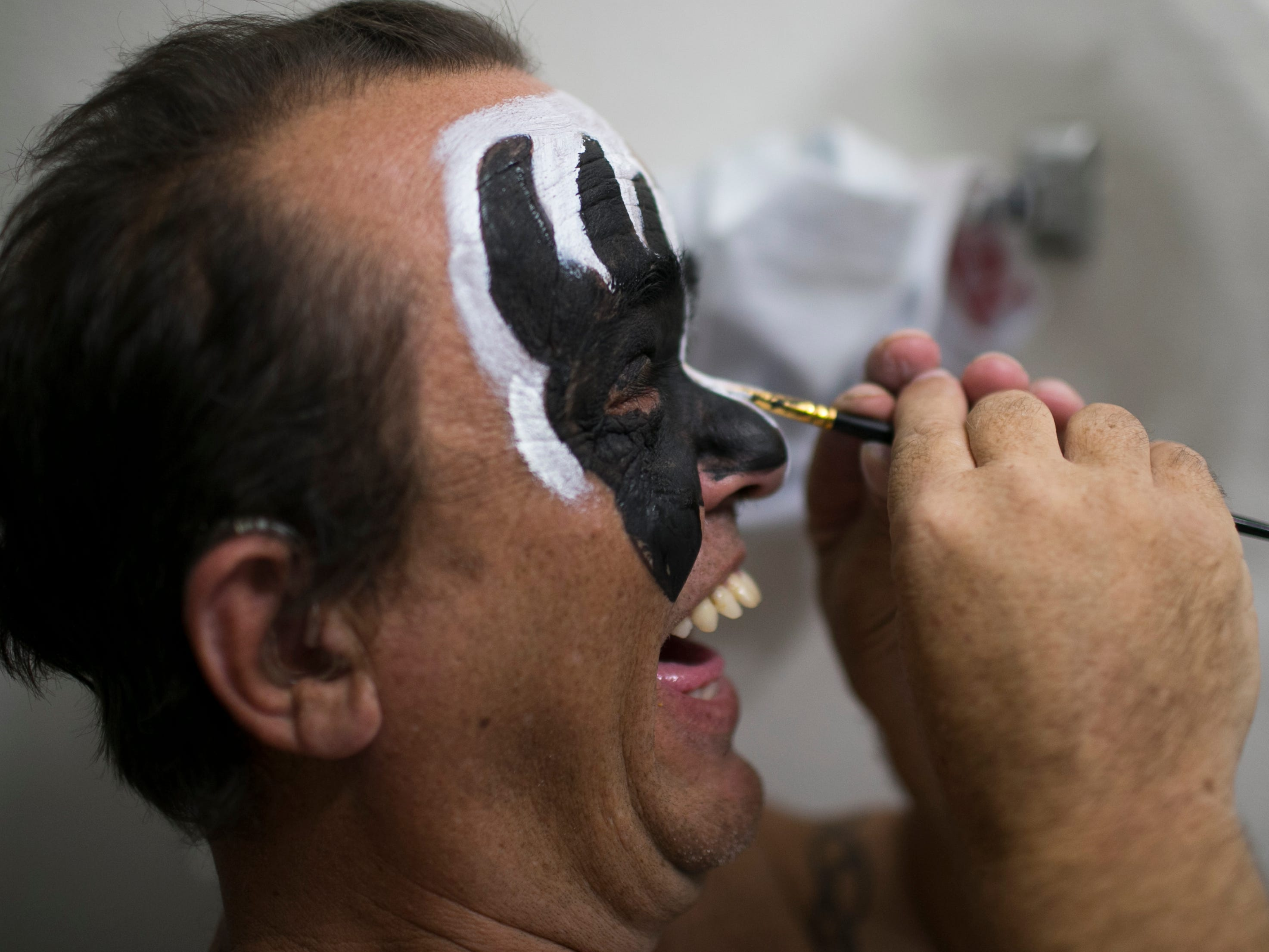 "Brian Thoe laughs as he puts on face make up before he performs as ""Mini-Gene"" with his band, Mini Kiss, at the Arizona State Fair in Phoenix on Saturday, Oct. 6, 2018."