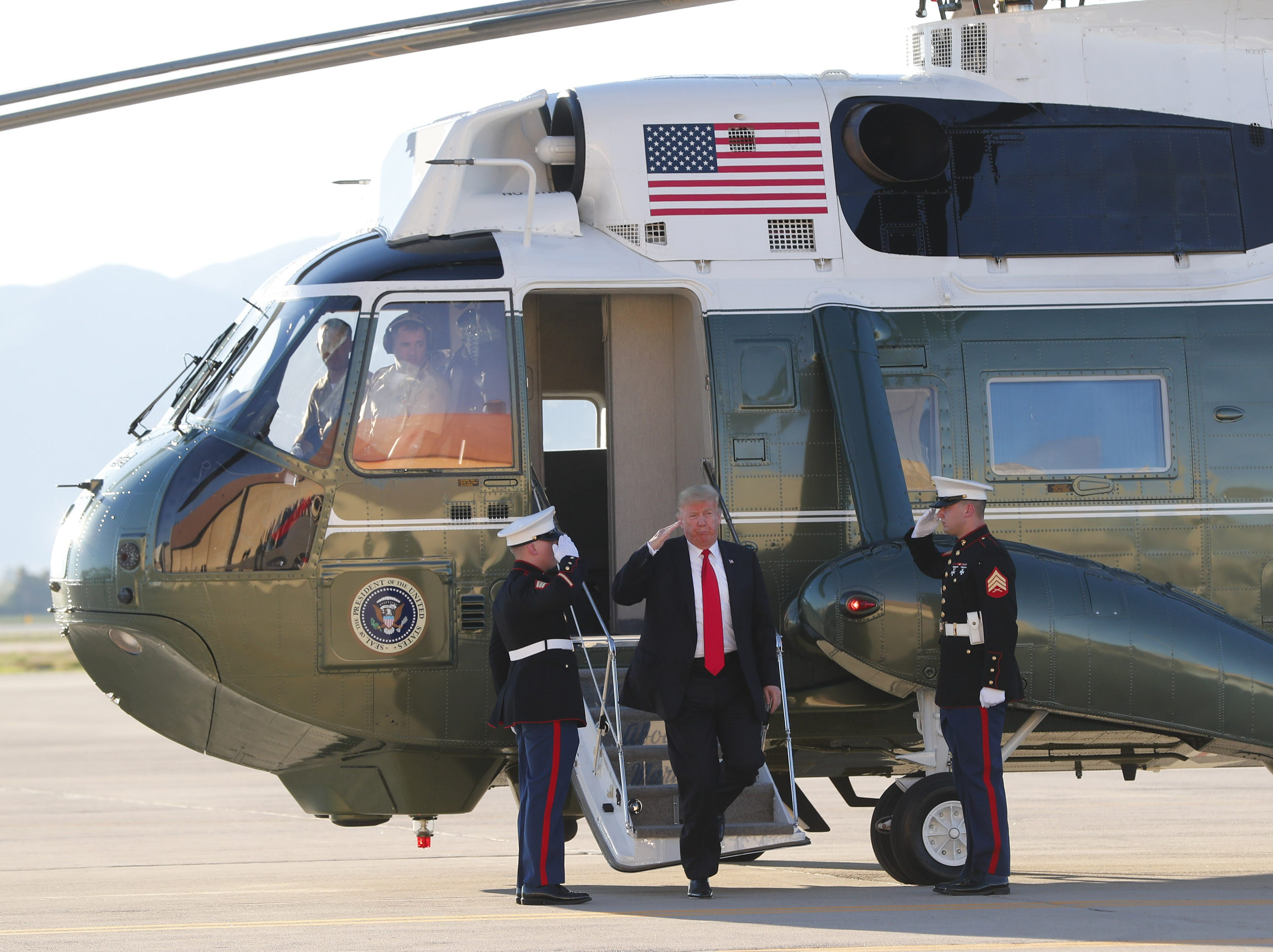 President Trump salutes while walking off Marine One during a defense capability and round-table tour at Luke Air Force Base in Glendale October 19, 2018.