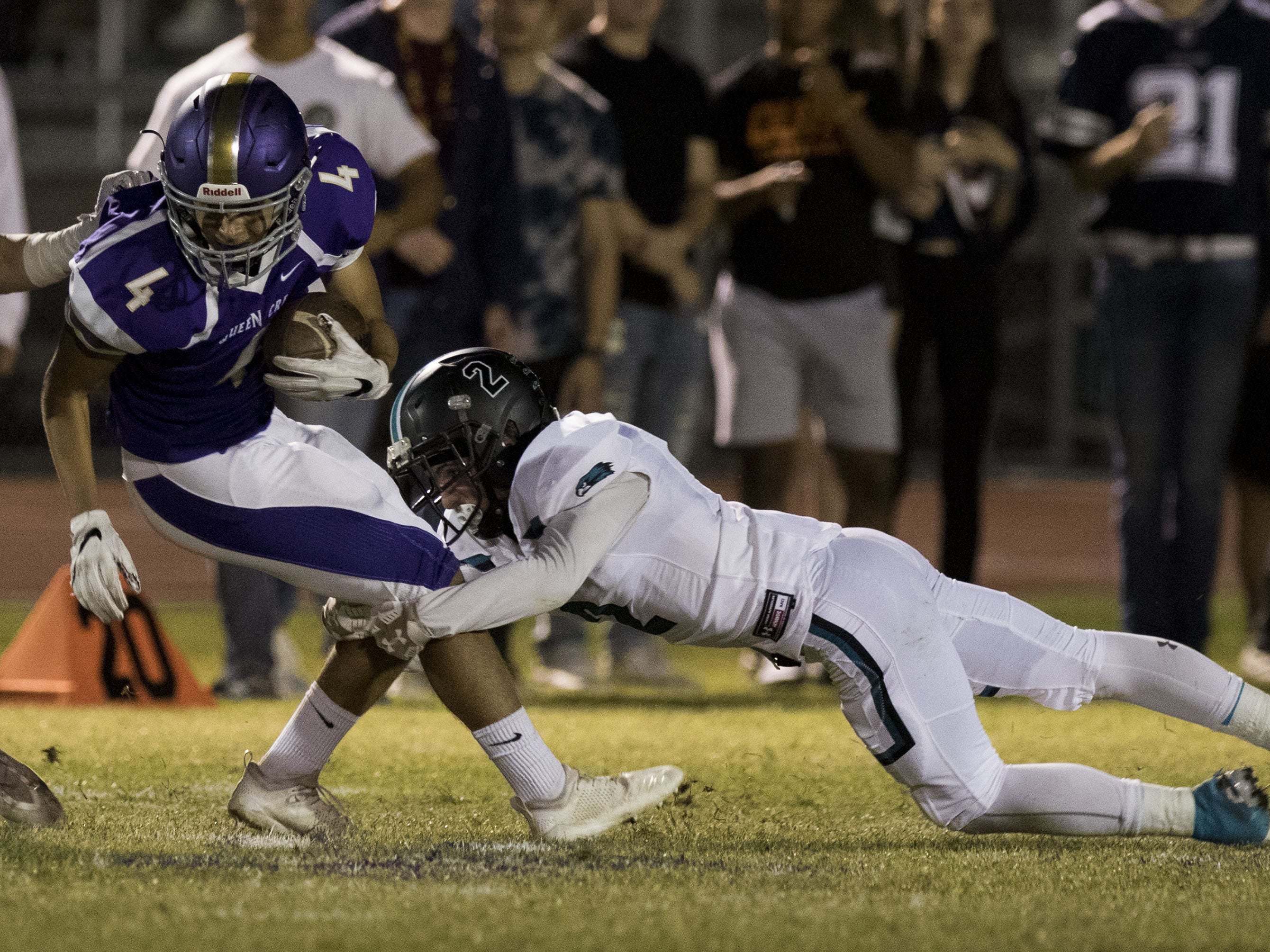 Queen Creek's Alec Prochazka gets tackled by Highland's Dayton Huffman in Queen Creek Friday, Oct. 19, 2018. #azhsfb