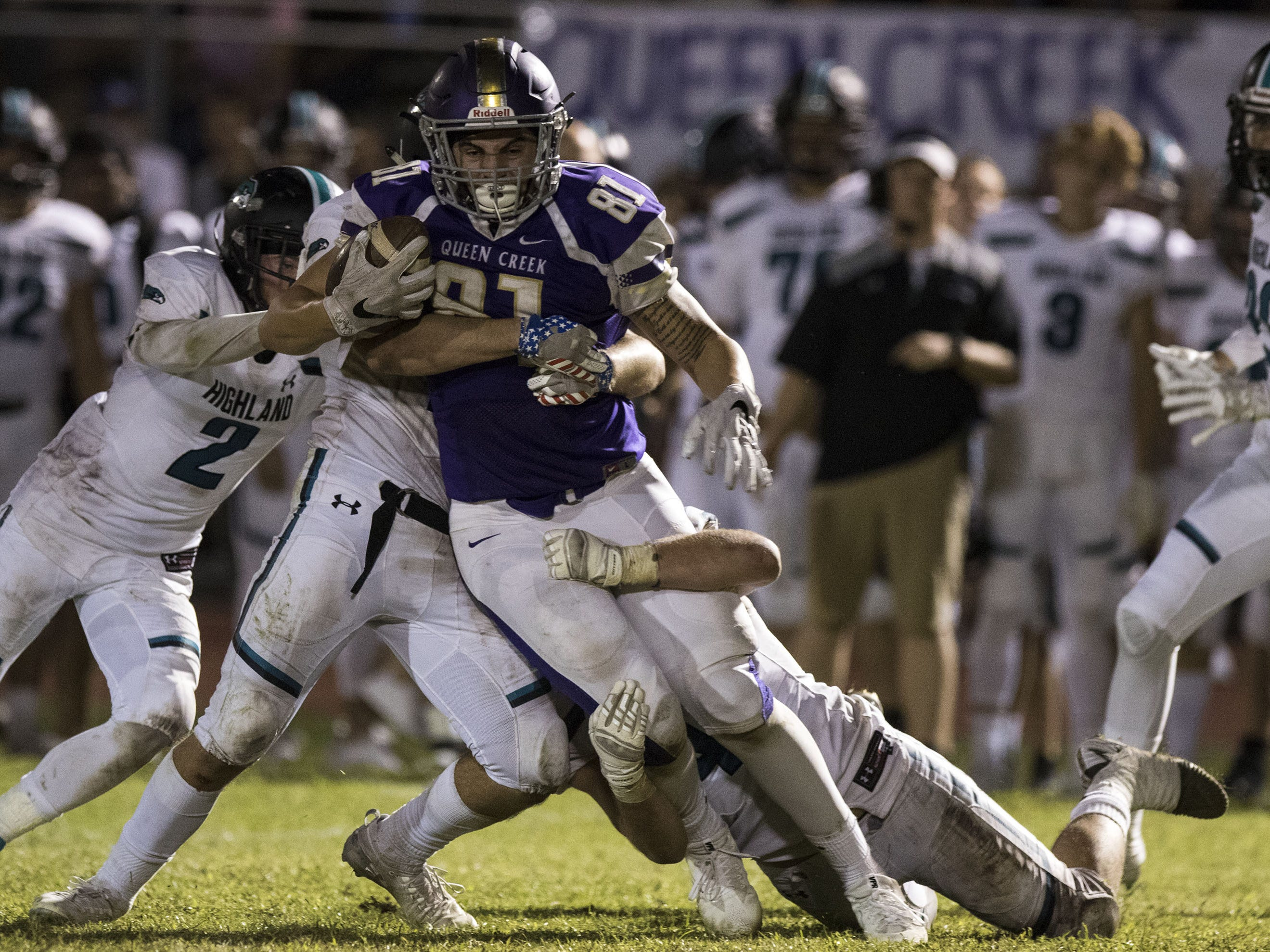 Queen Creek's Rafael Aldecoa gets wrangled by a pack of Highland defenders during their game in Queen Creek Friday, Oct. 19, 2018. #azhsfb