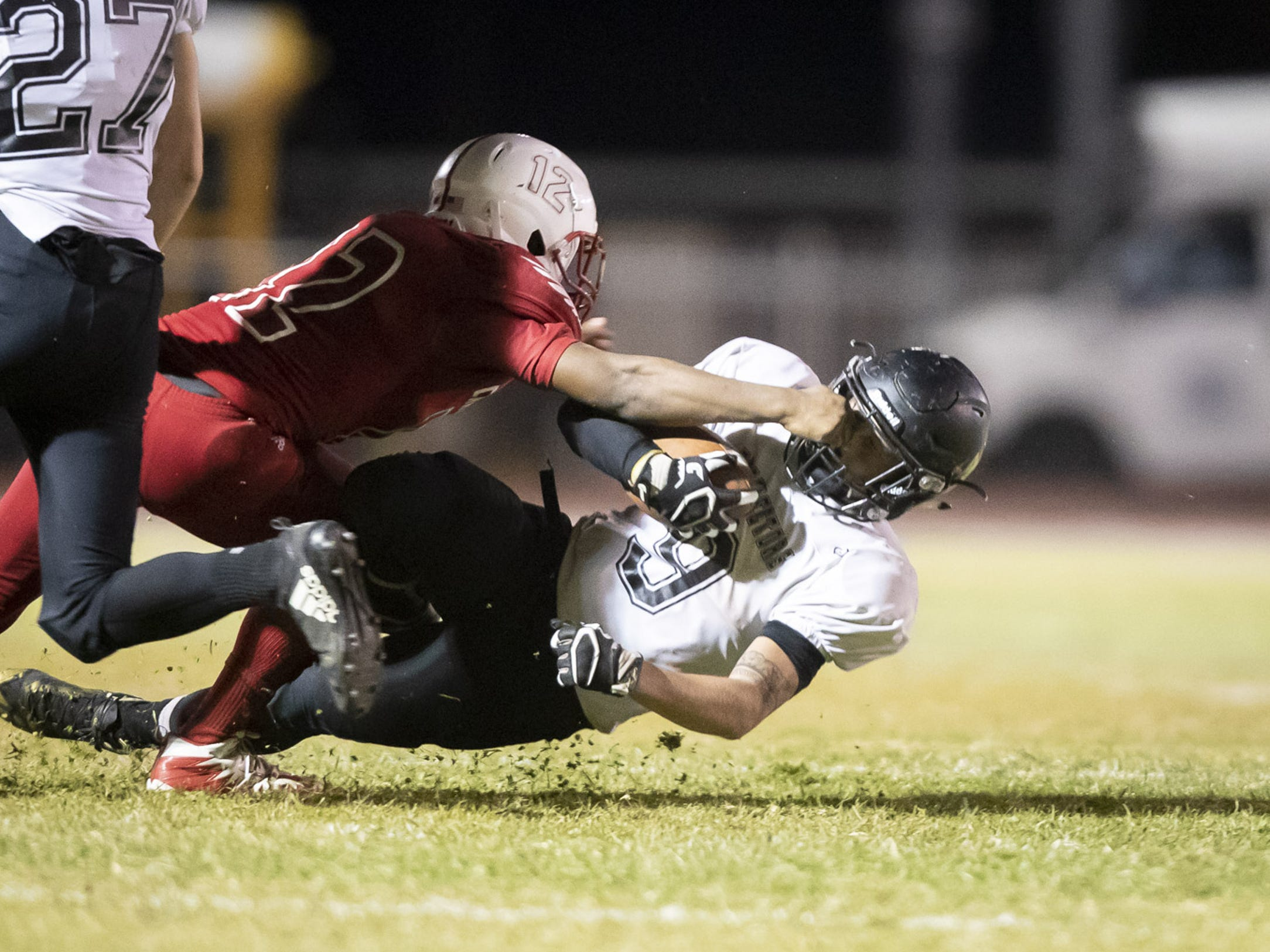 Junior cornerback Dimitri Taylor (12) of the Glendale Cardinals grabs the face mask of senior running back William Lohman (9) of the Apache Junction Prospectors at Glendale High School on Friday, October 19, 2018 in Glendale, Arizona. #azhsfb