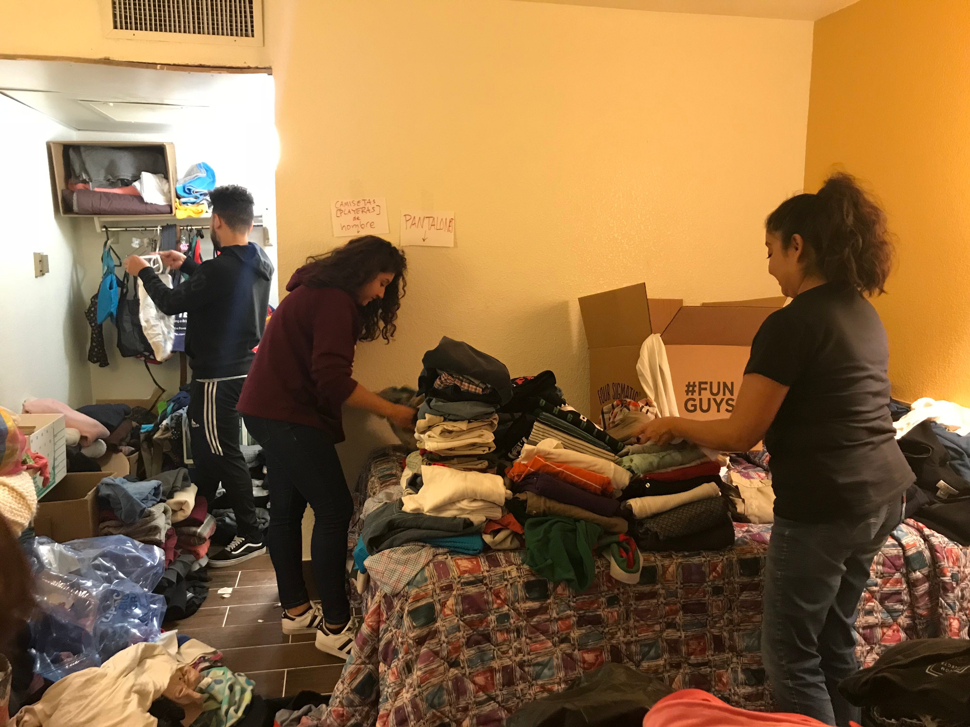 Raquel Vargas Lugo and her two children, Sylvia, 16, and Mark, 21, help sort donated clothes inside the room of a motel housing dozens of migrant families in Tucson.