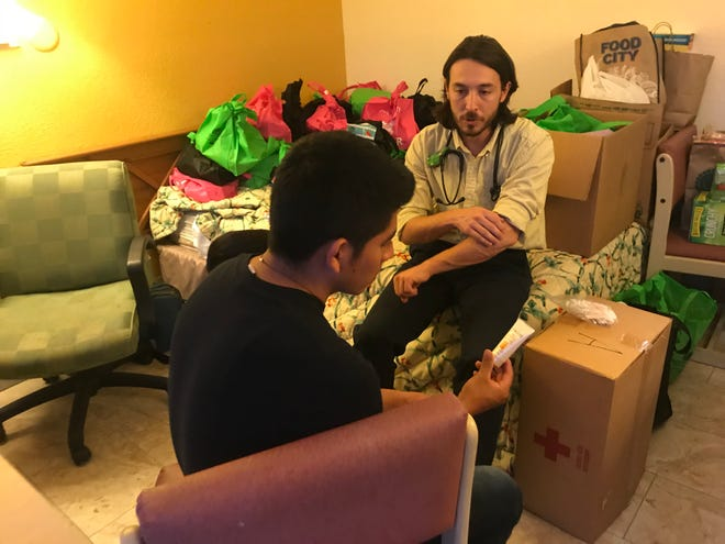 Anthony Favaloro, a second-year medical-school resident at the University of Arizona, instructs a Guatemalan migrant on how to treat some bumps on his skin, inside a room at a motel housing migrants in Tucson.