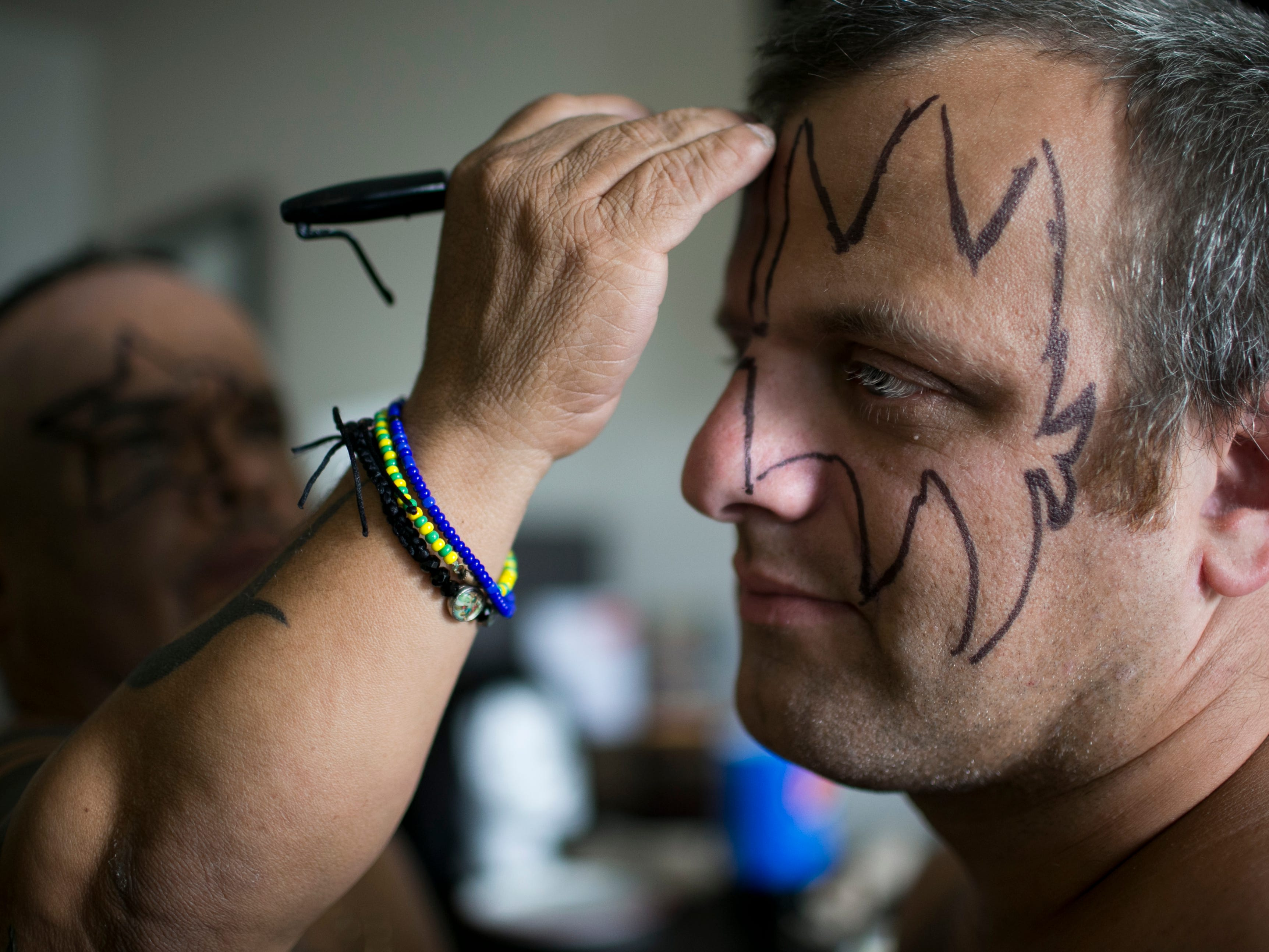 Pablo Montavlo (left) draws on the outline to Zachary Morris' (right) makeup before they perform with their group, Mini Kiss, at the Arizona State Fair in Phoenix on Saturday, Oct. 6, 2018.