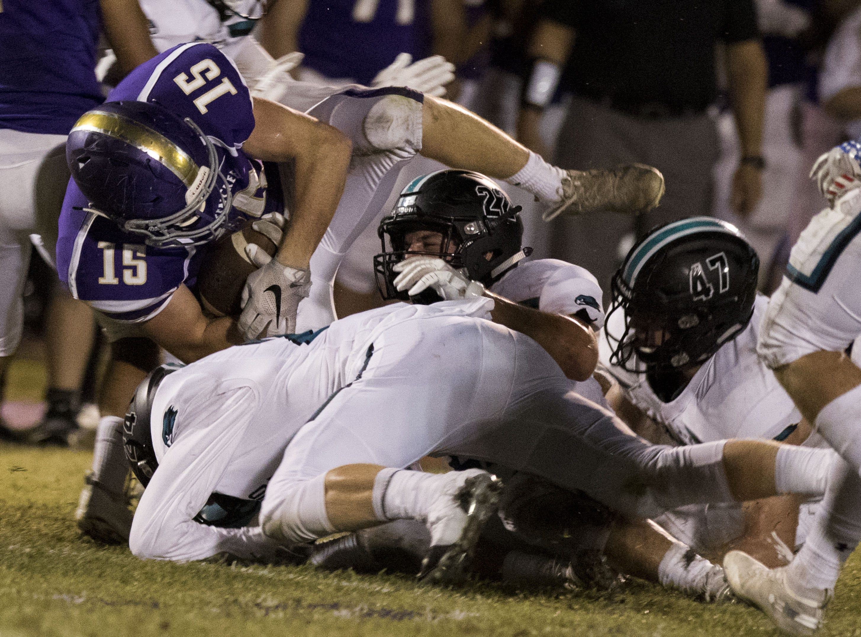 Queen Creek's Jacob Berry dives over a pile of Highland Hawks during them game in Queen Creek Friday, Oct. 19, 2018. #azhsfb