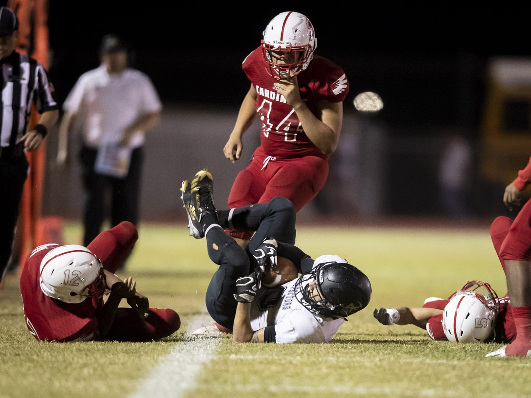 William Lohman (9) of the Apache Junction Prospectors is tackled after running the ball against the Glendale Cardinals at Glendale High School on Friday, Oct. 19, 2018 in Glendale, Arizona. #azhsfb