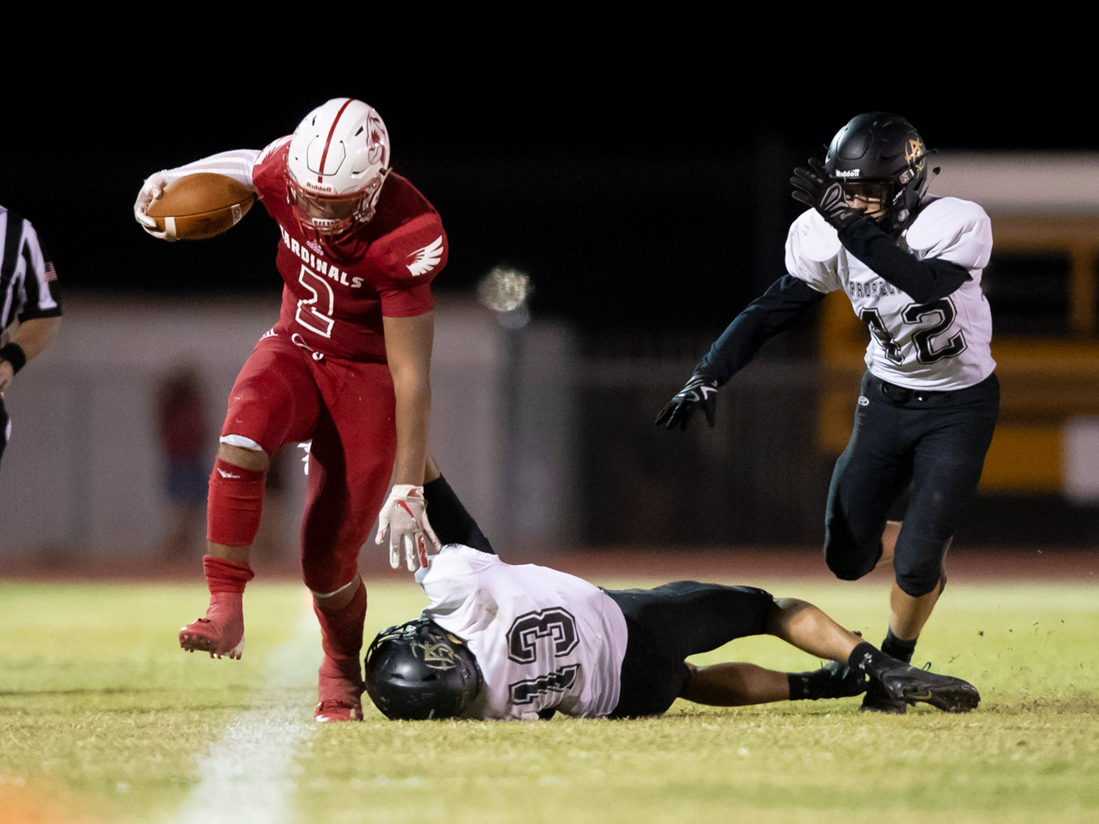Junior running back Kevin Daniels (2) of the Glendale Cardinals is brought down out of bounds by junior linebacker Talon Izbicki (13) of the Apache Junction Prospectors at Glendale High School on Friday, October 19, 2018 in Glendale, Arizona. #azhsfb