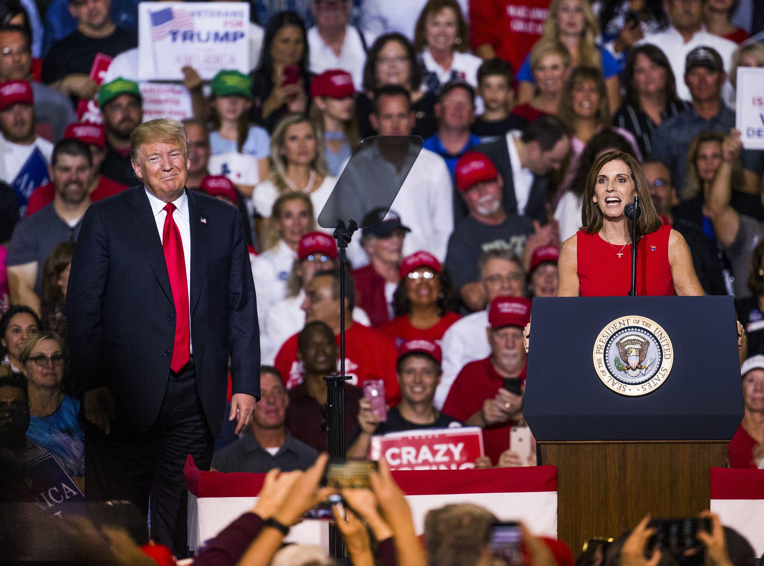 President Donald Trump joins Rep. Martha McSally on stage at the International Air Response Hangar at Phoenix-Mesa Gateway Airport on Oct. 19, 2018.
