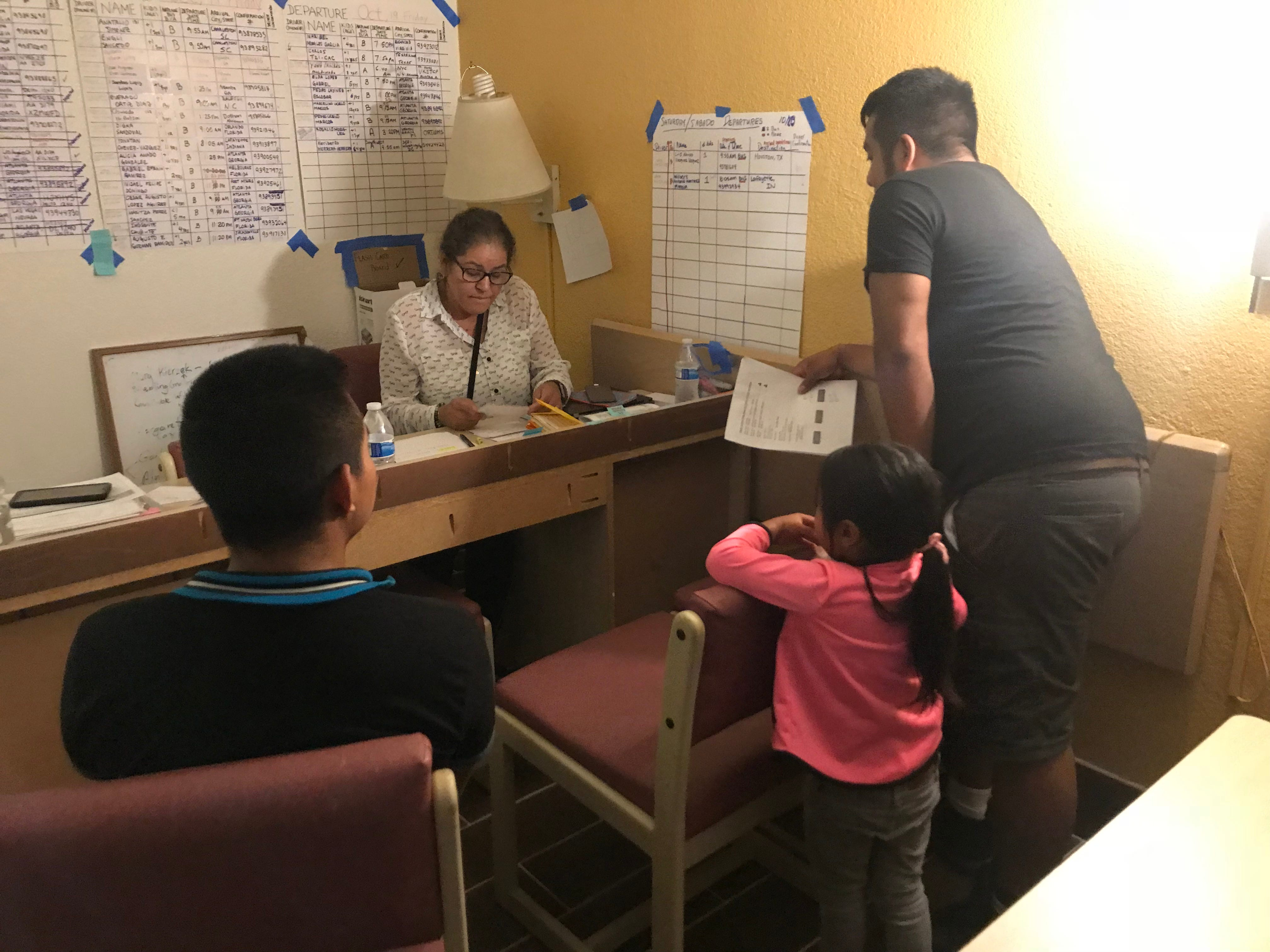A volunteer with Catholic Community Services in Tucson helps migrants finalize travel plans after they were released from immigration custody. The families are being housed inside a motel.
