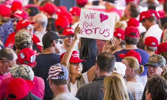 A woman waves a sign inside the International Air Response Hangar at Phoenix Mesa Gateway Airport, on Oct. 19, 2018. The crowd had several hours to wait for President Donald Trump to appear Friday evening for a rally supporting Senate candidate Rep. Martha McSally.