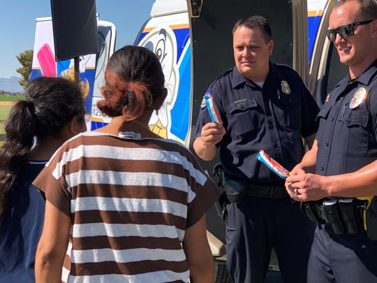 Policemen hand out popsicles to event-goers  during the unveiling of the ice cream van event on Oct. 20, 2018 at Lindo Park in Phoenix.