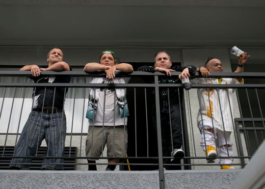 Zachary Morris (left) Brian Thoe (center left) Mark Mingolo (center right) and Pablo Montavlo (right) lean over their hotel balcony in Phoenix on Saturday, Oct. 6, 2018. Together, the four form the Kiss tribute band, Mini Kiss, and were performing at the Arizona State Fair that night.