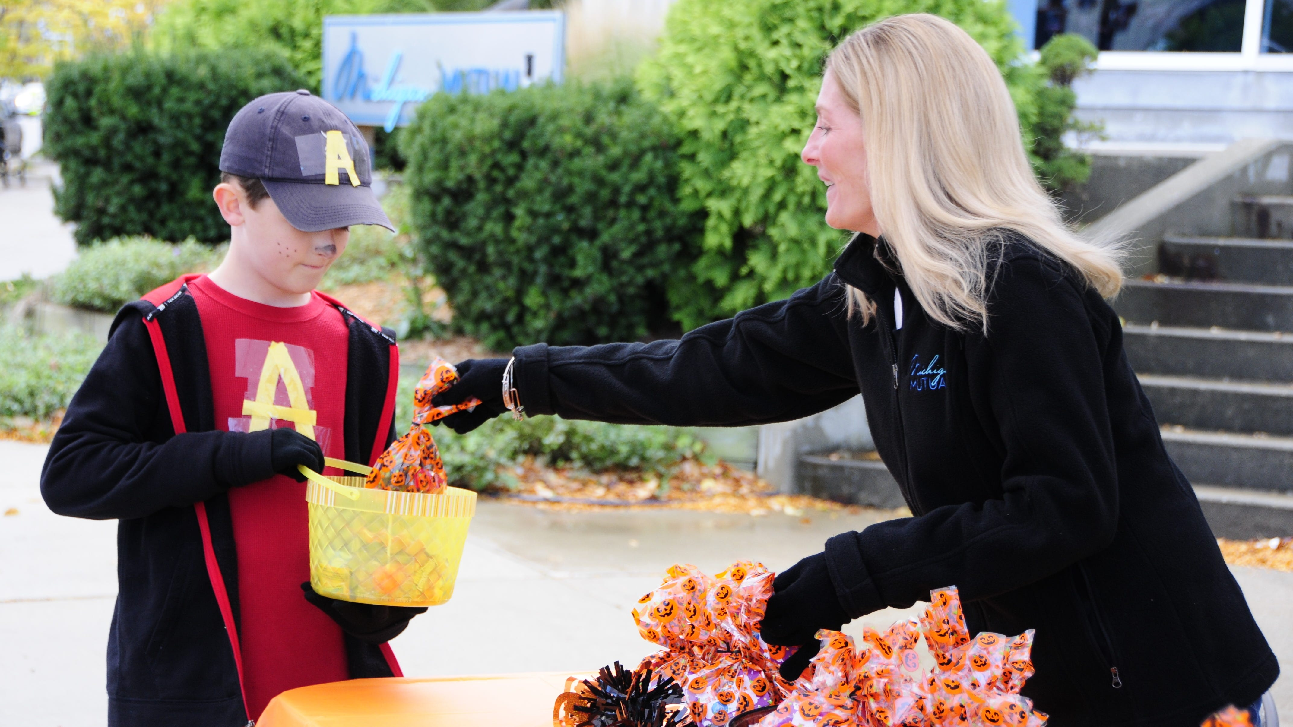 Audrey Torello of Michigan Mutual hands a bag of candy to Xander Koch, 10, of St. Clair during Truck-or-Treat, Saturday, Oct. 20, 2018 in downtown Port Huron.