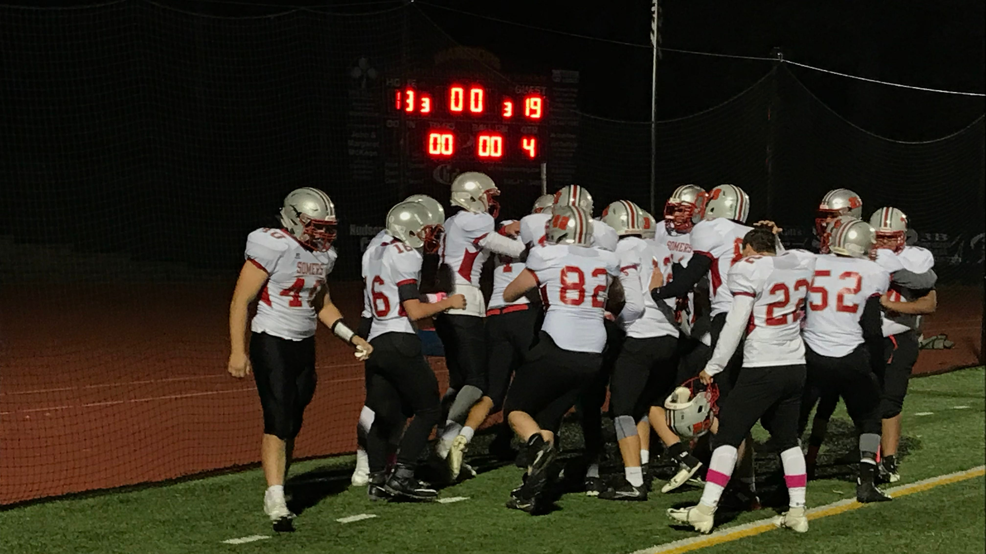 Members of the Somers High School football team swarm Lucas Fedele after he made the game-winning catch to defeat Our Lady of Lourdes on Friday.
