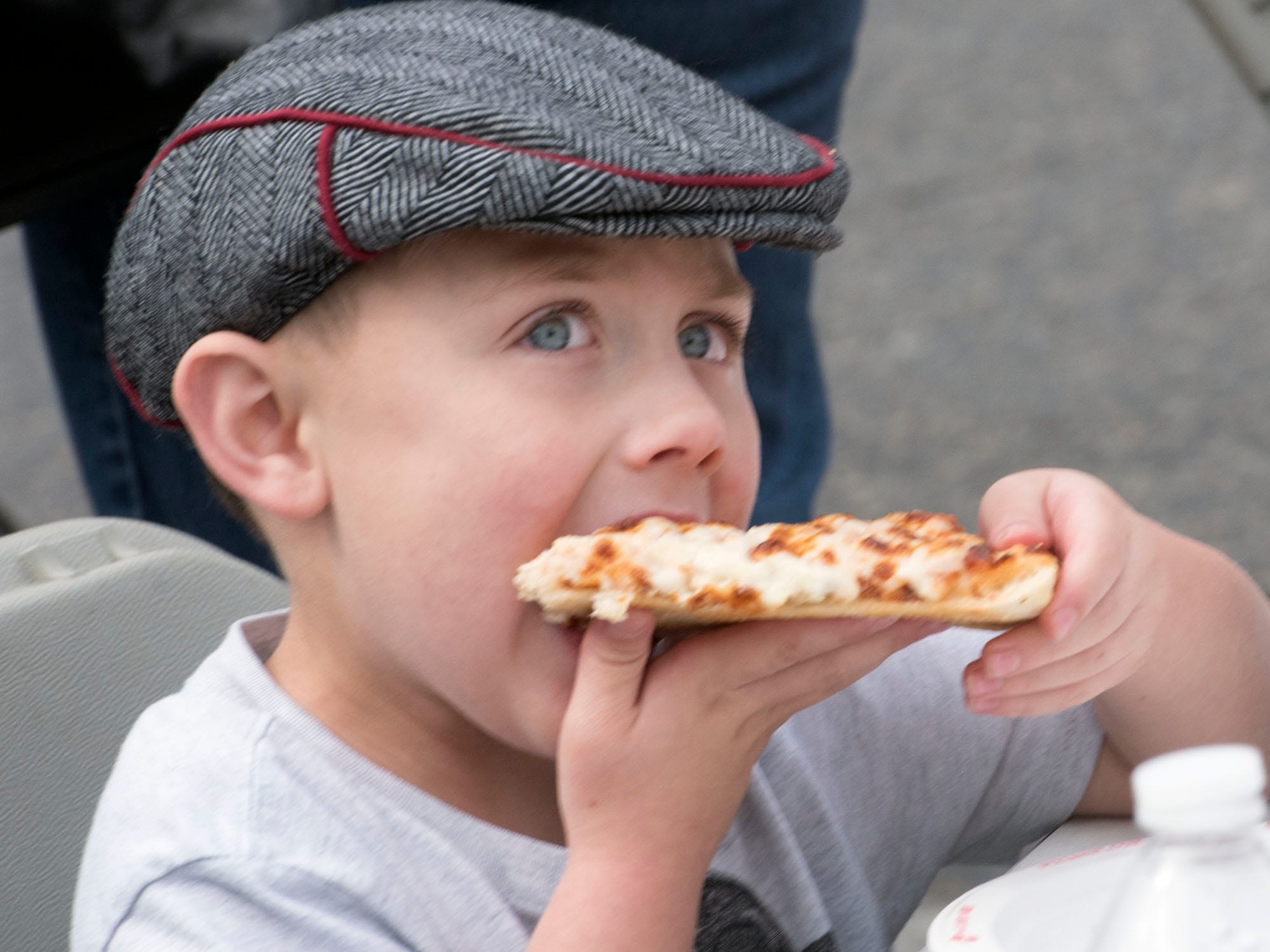 Four-year-old Jonathan Brindle eats pizza on Memorial Square. Applefest started Saturday morning October 20, 2018 in downtown Chambersburg.