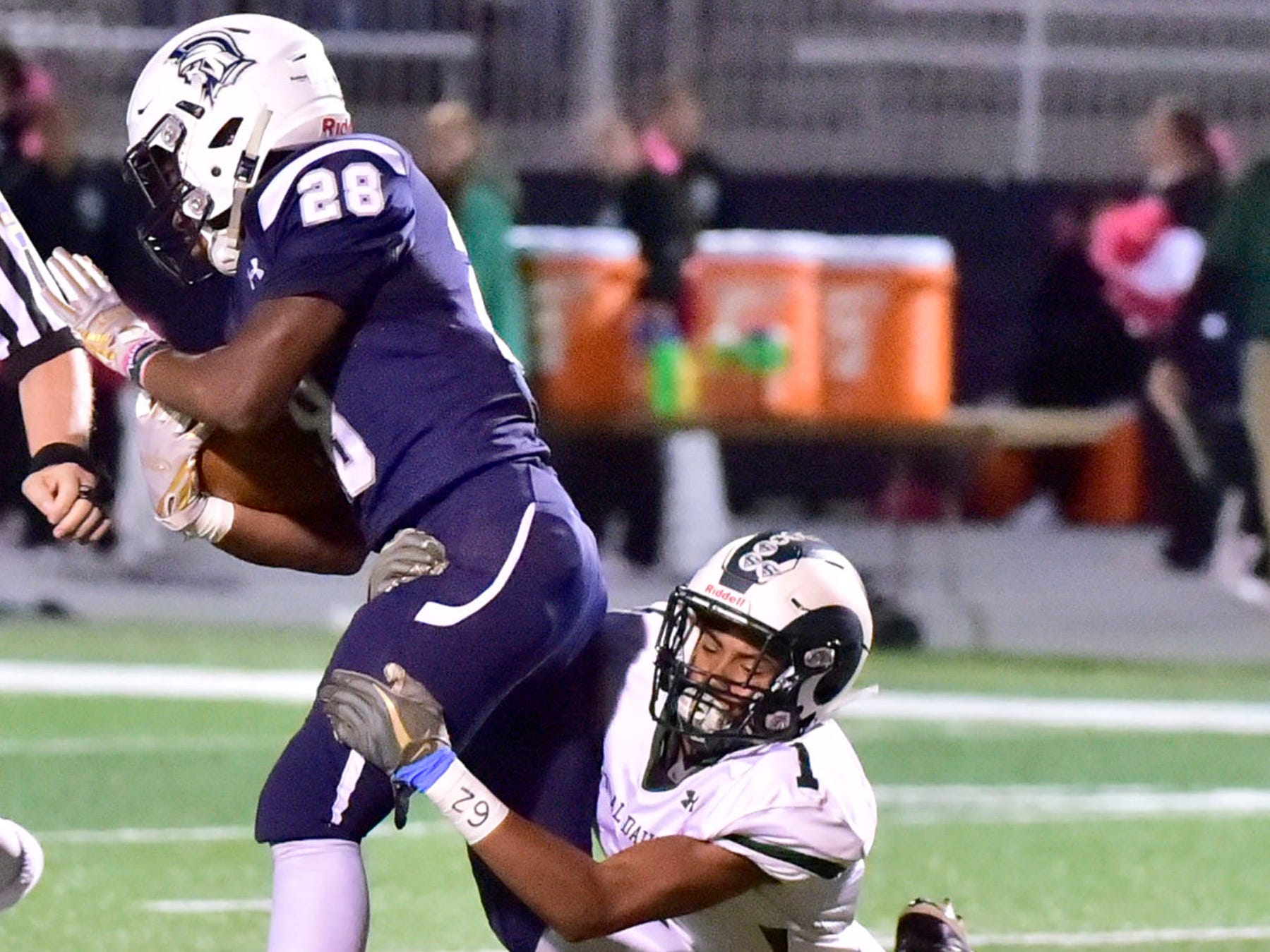 Chambersburg's Keyshawn Jones (28) tries to break away from CD's Tyrese Fuller (1). Chambersburg lost to Central Dauphin 35-14 in PIAA football on Friday, Oct. 19, 2018.