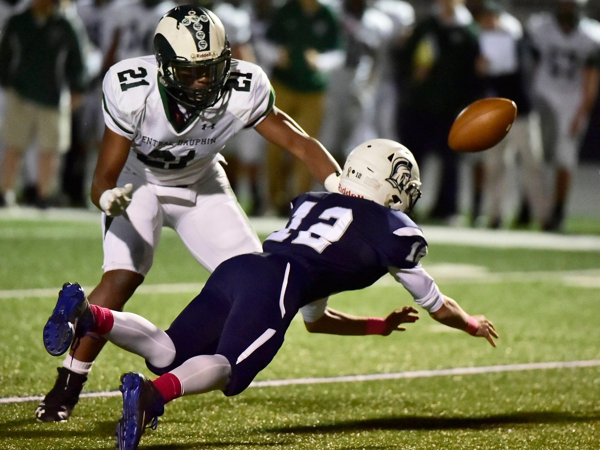 Chambersburg's Brady Stumbaugh (12) pitches a fumbled ball to a teammate as Amir Walton (21) of CD defends. Chambersburg lost to Central Dauphin 35-14 in PIAA football on Friday, Oct. 19, 2018.
